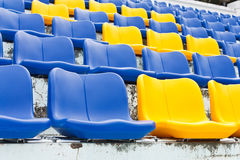 Blaue und gelbe leere Plastiksitze Stockfotografie