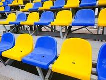 Blaue und gelbe Plastikstühle auf der Straße oder am Stadion stockfotografie