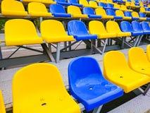 Blaue und gelbe Plastikstühle auf der Straße oder am Stadion lizenzfreies stockfoto