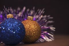 Blaue und goldene Weihnachtsbälle mit einer Girlande Nette Dekorationen Stockfotografie