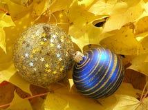 Blaue und goldene Weihnachtskugeln mit goldenen Strudeln und Anfängen in den Ahornblättern Lizenzfreies Stockfoto