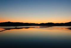Blaue und orange Abstufung des Sonnenuntergangs auf dem JINYANG-See Stockfotografie