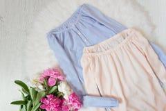 Blaue und rosa Bluse mit entlüftete Schultern und ein Blumenstrauß von Pfingstrosen Modernes Konzept, weißer Pelz auf dem Hinterg Stockbild