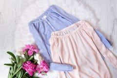 Blaue und rosa Bluse mit entlüftete Schultern und ein Blumenstrauß von Pfingstrosen Modernes Konzept, weißer Pelz auf dem Hinterg Lizenzfreie Stockfotos