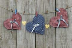 Blaue und rosa Herzen, die an der Wäscheleine hängen Stockbild