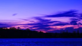 Blaue und rosa Wolken im Abstand über dem Meer lizenzfreie stockfotografie
