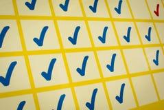 Blaue und rote Prüfzeichen im gelben Gitter Lizenzfreies Stockfoto