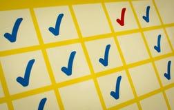 Blaue und rote Prüfzeichen im gelben Gitter Lizenzfreie Stockbilder