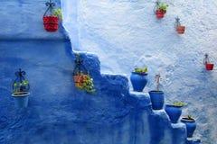 Blaue und rote Töpfe mit Blumen in der blauen Stadt Stockbild