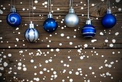 Blaue und silberne Weihnachtsbälle mit Schnee Stockfotos