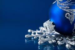Blaue und silberne Weihnachtsverzierungen auf dunkelblauem Hintergrund Stockfotografie