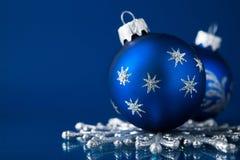 Blaue und silberne Weihnachtsverzierungen auf dunkelblauem Hintergrund mit Raum für Text Lizenzfreies Stockbild
