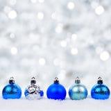Blaue und silberne Weihnachtsverzierungen im Schnee mit funkelndem Hintergrund Stockfotos