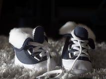 Blaue und weiße Kind-` s Schuhe auf einem dunklen Hintergrund stockfotografie