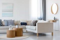 Blaue und weiße Malerei und Spiegel im Holzrahmen im eleganten Wohnzimmerinnenraum mit Ecksofa und Couchtisch stockfotografie