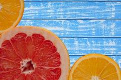 Blaue und weiße Pampelmuse des hölzernen Hintergrundes und Orange Stockfotografie