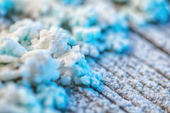 Blaue und weiße Schneeflocken auf hölzernem Hintergrund mit Schnee, Weihnachtstapete Lizenzfreies Stockbild