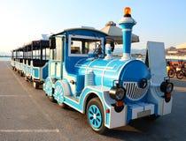 Blaue und weiße touristische Exkursionslokomotive auf Seestrand in Griechenland Lizenzfreies Stockfoto