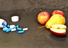 Blaue und weiße Vitamine in den Kapseln und in den roten Äpfeln sind auf dem Tisch lizenzfreie stockbilder