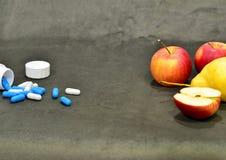 Blaue und weiße Vitamine in den Kapseln und in den roten Äpfeln sind auf dem Tisch lizenzfreies stockfoto