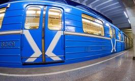 Blaue Untergrundbahn, die am U-Bahnhof steht Breites angl Stockfoto