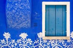 Blaue Wand, geschlossener Fensterladen eines Fensters, mit Spitzeverzierung Stockfotos