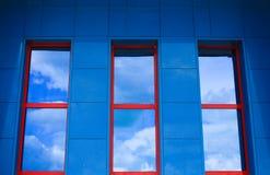 Blaue Wand mit drei roten Fenstern, die Himmel reflektieren stockfoto