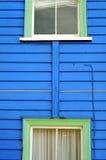 Blaue Wand mit grünen Fenstern Stockbilder
