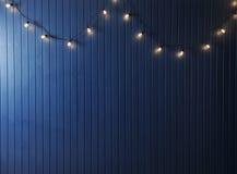 Blaue Wand mit Retro- Girlande von Glühlampen Beschaffenheit für den Entwurf Lizenzfreie Stockfotos