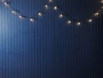 Blaue Wand mit Retro- Girlande von Glühlampen Beschaffenheit für den Entwurf Stockfoto