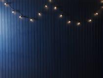 Blaue Wand mit Retro- Girlande von Glühlampen Beschaffenheit für den Entwurf Lizenzfreie Stockfotografie
