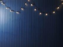 Blaue Wand mit Retro- Girlande von Glühlampen Beschaffenheit für den Entwurf Stockbild