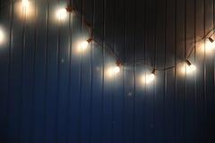 Blaue Wand mit Retro- Girlande von Glühlampen Beschaffenheit für den Entwurf Lizenzfreies Stockbild