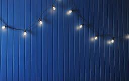 Blaue Wand mit Retro- Girlande von Glühlampen Beschaffenheit für den Entwurf Stockfotos