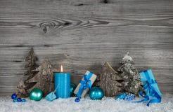 Blaue, weiße und graue Weihnachtsdekoration mit einem brennenden candl Stockfotos