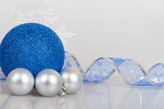 Blaue Weihnachtsbälle mit weißen Schneeflocken Stockfotos