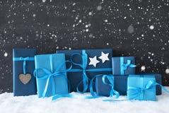 Blaue Weihnachtsgeschenke, schwarze Zement-Wand, Schnee, Schneeflocken Stockfotos