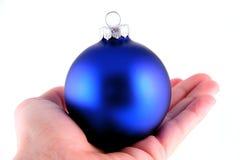 Blaue Weihnachtskugel in der Hand Stockfotos
