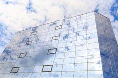 Blaue Wolken und Sonne werden in den Gläsern von Fenstern eines modernen Gebäudes reflektiert Stockbilder