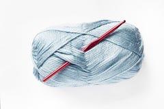 Blaue Wolle und rote Häkelnadel Lizenzfreie Stockfotografie