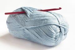 Blaue Wolle und rote Häkelnadel Lizenzfreie Stockbilder