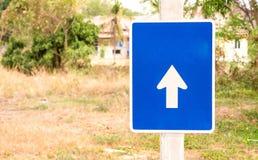 Blaue Zeichen mit Pfeilen, Unschärfebaumhintergrund Stockbilder
