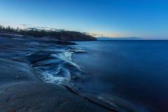 Blauer Abend auf der Seefelsigen Küste Stockbilder