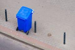 Blauer Abfalleimer auf Straßenpflasterung Lizenzfreie Stockfotos