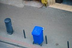 Blauer Abfalleimer auf Straßenpflasterung Stockfotos