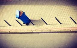 Blauer Abfalleimer auf Straßenpflasterung Stockfotografie