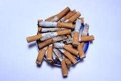 Blauer Aschenbecher füllte mit verwendeten Zigarettenkippen auf weißem und blauem Hintergrund Stockbild