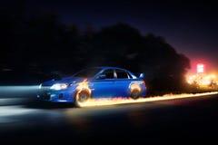 Blauer Auto-Antrieb auf Asphaltlandschaftsstraße mit Feuer dreht sich nachts Stockbild