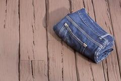 Blauer Baumwollstoff mit Abnutzung - hölzerner Hintergrund stockbilder
