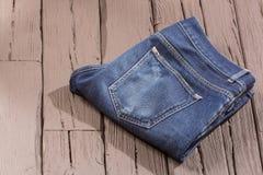 Blauer Baumwollstoff mit Abnutzung - hölzerner Hintergrund lizenzfreies stockbild